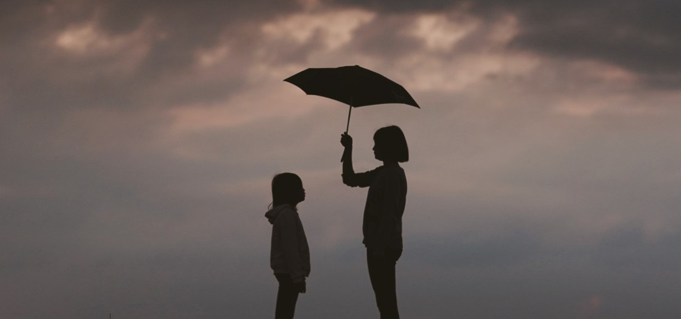 woman holding umbrella with girl